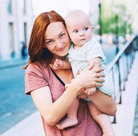 Red headed woman holding a small baby grinning