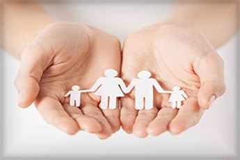Open hands holding a cut-out paper family